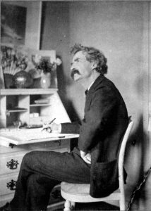 800px-mark_twain_pondering_at_desk